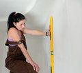 Woman finding a straight line spirit level with holding iagainst wall in the vertical position while renovating her house Royalty Free Stock Images