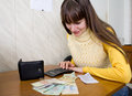 Woman finds balances money using calculator Stock Photo