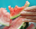 Woman fingers kept a piece of watermelon. Stock Photography