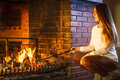 Woman with fire iron poker at home fireplace. Royalty Free Stock Photo