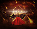 Woman fire mage conjured fiery meteor rain in medieval dress with developing mantle Royalty Free Stock Image