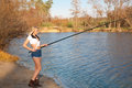 Woman fishing in river pretty girl shorts with a rod on the sandy shore of the autumn Royalty Free Stock Photos