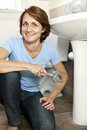 Woman fixing plumbing confident repairing sink in bathroom at home Royalty Free Stock Photos