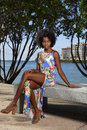 Woman in floral pattern dress sitting on park bench beauty afro hairstyle Royalty Free Stock Photo