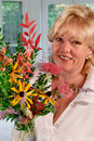 Woman with flower arrangement Stock Images