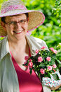 Woman and flowers a mature sunny day Stock Photography