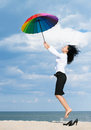 Woman flying away from her problems with a colorful umbrella out of office concept Royalty Free Stock Photography