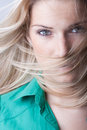 Woman with flying blond hair eyes of a beautiful young her long in the breeze and whipping across her mouth and face Royalty Free Stock Photo