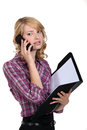 Woman with folder making telephone call Stock Photo