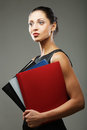 Woman with folders over gray background young Stock Image