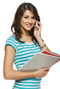 Woman with folders talking on mobile phone Royalty Free Stock Image