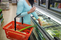Woman with food basket at grocery store freezer Royalty Free Stock Photo