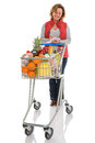 Woman food shopping with trolley isolated a a supermarket full of fresh checking her list on a white background Royalty Free Stock Photography