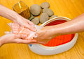 Woman foot in paraffin bath at the spa treatment Stock Photography