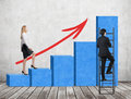 A woman in formal clothes is going up through a blue bar chart while a man has found a shortcut how to reach the final point of t Royalty Free Stock Photo