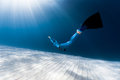 Woman freediver glides over sandy bottom Royalty Free Stock Photo