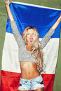 Woman with french flag young holding a against a green wall background lifestyle Stock Photography
