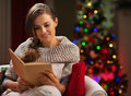 Woman in front of Christmas tree reading book Royalty Free Stock Images