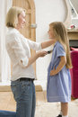 Woman in front hallway brushing young girl's hair Royalty Free Stock Photos
