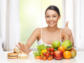 Woman with fruits rejecting junk food healthy and concept hamburger and cake Stock Photos