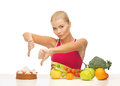 Woman with fruits showing thumbs down to cake healthy food Stock Images
