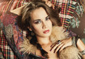 Woman with fur pelt a lying on a sofa a around her neck and a paisley pattern dress Stock Photos