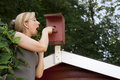 Woman in garden controls bird house blond Royalty Free Stock Photography