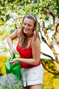 Woman in garden watering flowers Stock Photos
