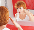 Woman gets cream on face mature in bathroom adult female looking at mirror Royalty Free Stock Images