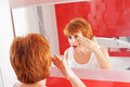 Woman gets cream on face mature in bathroom adult female looking at mirror Royalty Free Stock Photo