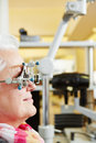 Woman gets examination at senior with trial frame ophthalmologist Royalty Free Stock Photo