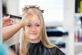 Woman getting hair combed mirror reflection of young her before haircut at parlor Stock Images
