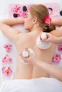 Woman getting herbal compress ball therapy beautiful young at spa salon Stock Images