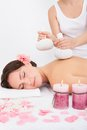 Woman getting herbal compress ball therapy beautiful young at spa salon Royalty Free Stock Photos