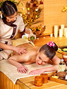 Woman getting massage in bamboo spa. Royalty Free Stock Photography