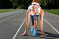 Woman getting ready to start on stadium summer outdoors training Royalty Free Stock Images