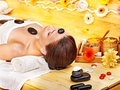 Woman getting stone therapy massage . Stock Photo