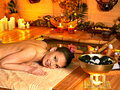 Woman getting stone therapy massage in bamboo spa Stock Images