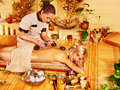 Woman getting stone therapy massage in bamboo spa Royalty Free Stock Photography