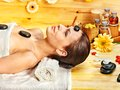 Woman getting stone therapy massage in wooden spa Royalty Free Stock Image