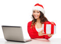 Woman with gift box and laptop computer christmas x mas online shopping concept in santa helper hat Stock Photo