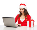 Woman with gift box and laptop computer christmas x mas online shopping concept in santa helper hat Royalty Free Stock Image