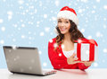 Woman with gift box and laptop computer christmas x mas online shopping concept in santa helper hat Stock Photography