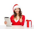 Woman with gift box and tablet pc computer christmas x mas online shopping concept in santa helper hat Royalty Free Stock Photography
