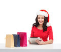 Woman with gift box and tablet pc computer christmas x mas online shopping concept in santa helper hat Royalty Free Stock Photo