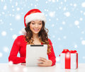 Woman with gift box and tablet pc computer christmas x mas online shopping concept in santa helper hat Royalty Free Stock Photos
