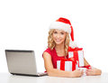 Woman with gift boxes and laptop computer christmas x mas online shopping concept in santa helper hat Stock Photo