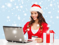 Woman with gift laptop computer and credit card christmas x mas online shopping concept in santa helper hat box Royalty Free Stock Images