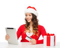 Woman with gift tablet pc and credit card christmas x mas online shopping concept in santa helper hat box computer Stock Photo