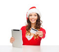 Woman with gift tablet pc and credit card christmas x mas online shopping concept in santa helper hat box computer Stock Images